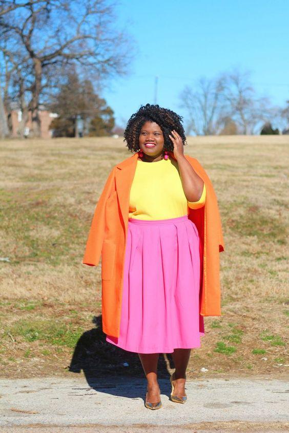 Ein Farbblock-Outfit mit einem gelben Oberteil, einem rosa Plissee-Midi, einem orangefarbenen Mantel und metallischen Schuhen