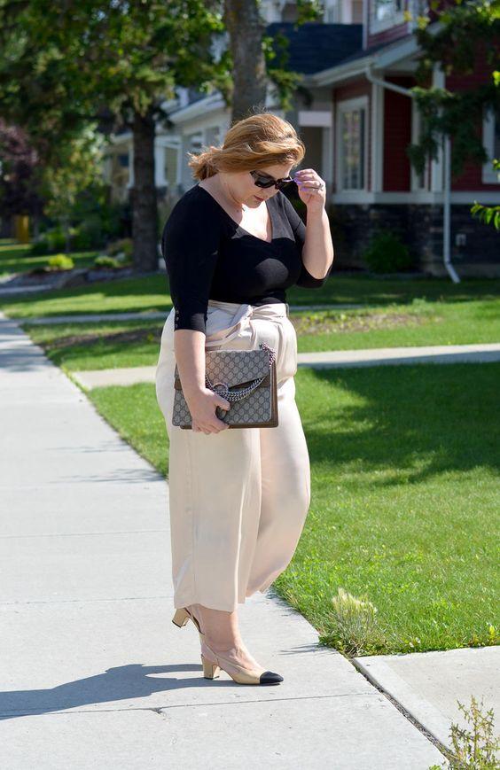 ein schwarzes langärmliges Top, cremige Culottes, cremefarbene und schwarze Schuhe und eine große Tasche