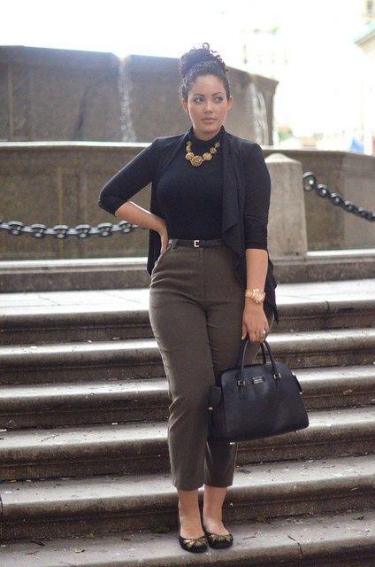 kurze grüne Hosen, ein schwarzes Top, eine schwarze Strickjacke, eine Statement-Kette, eine schwarze Tasche und Wohnungen