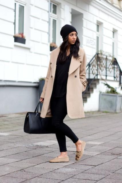 Mit schwarzem Hut, schwarzer Hose, Einkaufstasche und Pullover