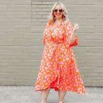 ein leuchtend orangefarbenes Wickel-Midi-Kleid mit Blumendruck, asymmetrischem Rock und transparenten Absätzen
