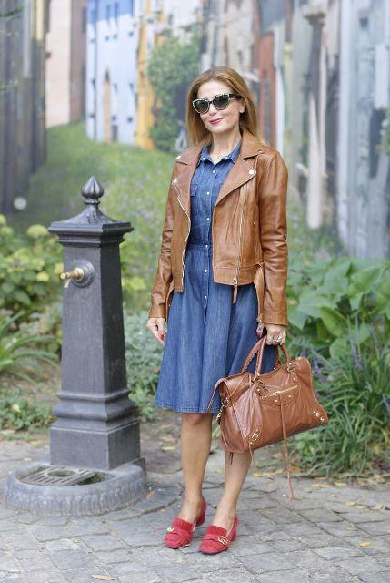Mit knielangem Jeanskleid, brauner Lederjacke und brauner Ledertasche